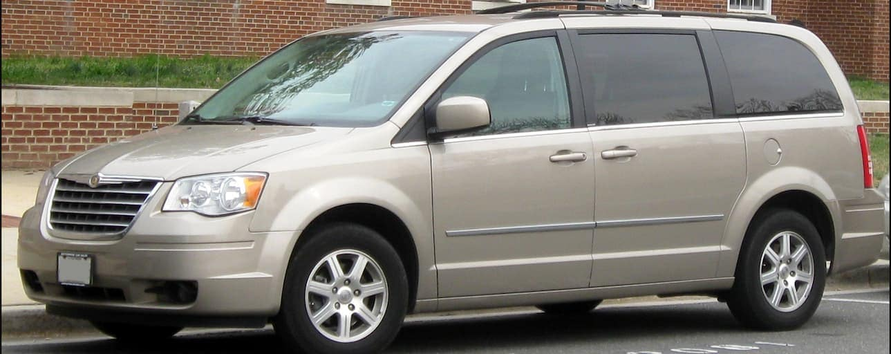 A silver 2010 used Chrysler Town & Country is parked in front of a brick building near Cincinnati, OH.