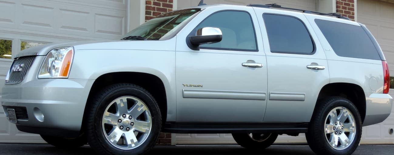 A silver 2011 used GMC Yukon is parked in front of a garage near Cincinnati, OH.