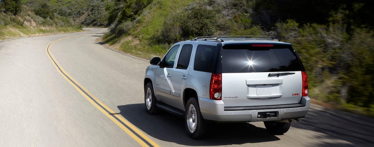A silver 2013 used GMC Yukon is driving on a highway with blurred trees next to it.
