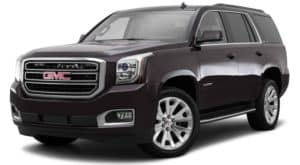 A black 2015 used GMC Yukon is facing left.