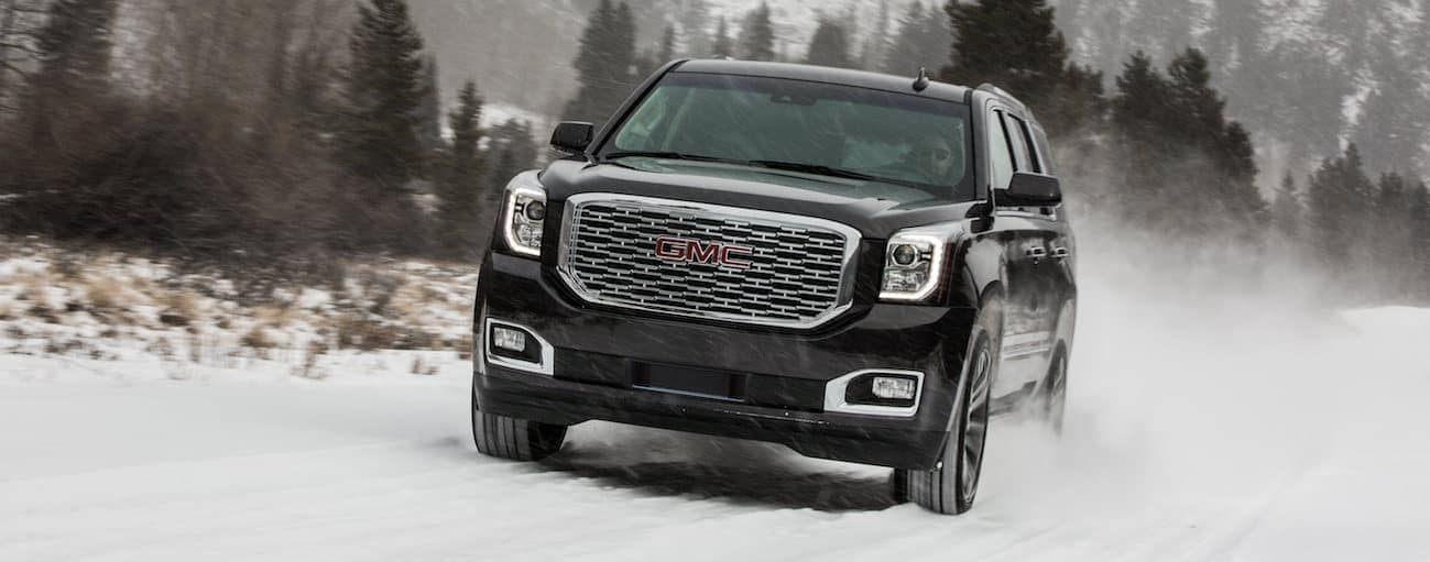 A 2019 used GMC Yukon is driving through a snow storm.