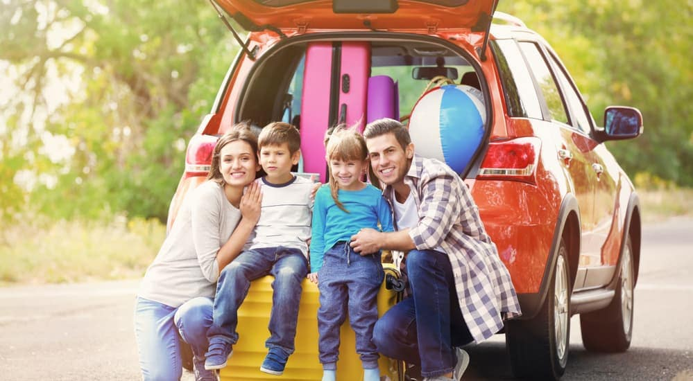 A family is smiling in front of a red car after their test drive.