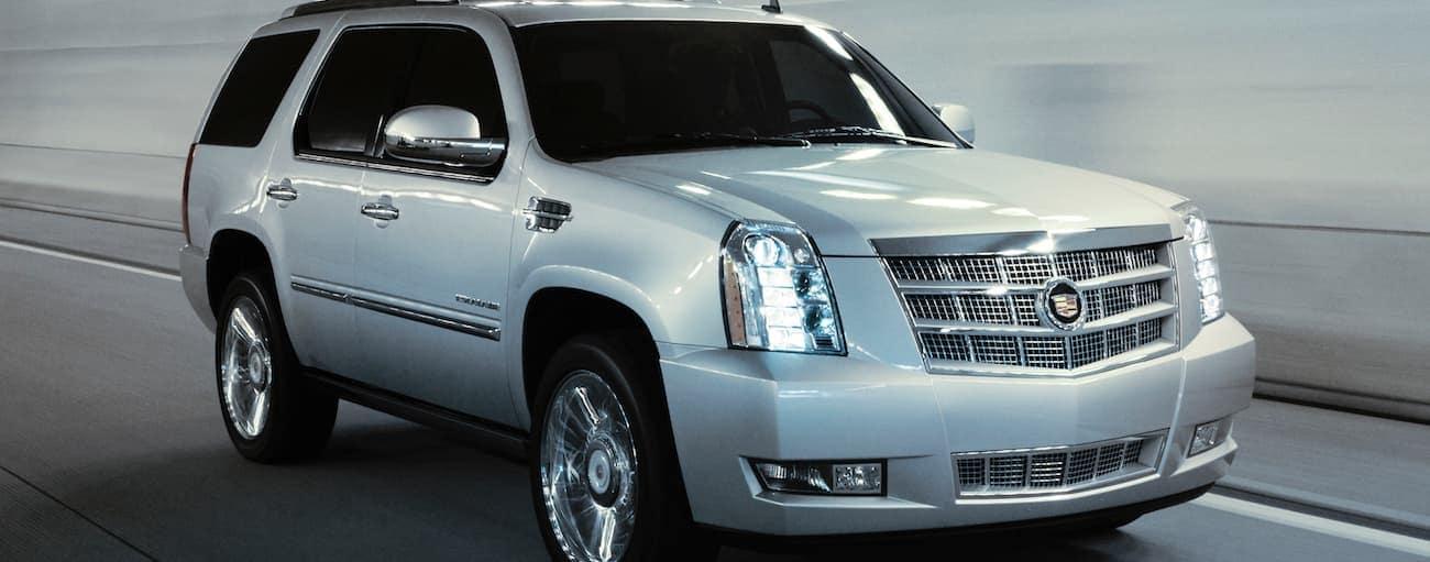 A silver 2013 Cadillac Escalade is driving through a city tunnel in Cincinnati, OH.