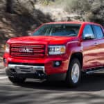 A red 2015 GMC Canyon is driving past a hill.