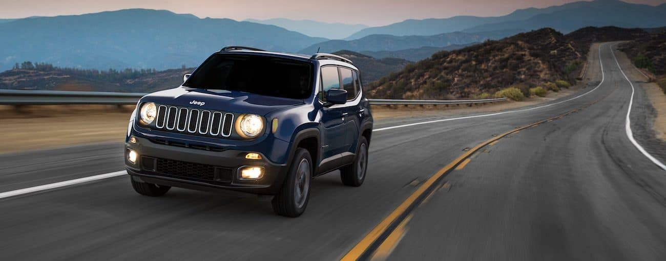 A dark blue 2017 Jeep Renegade is driving on a highway overlooking mountains.