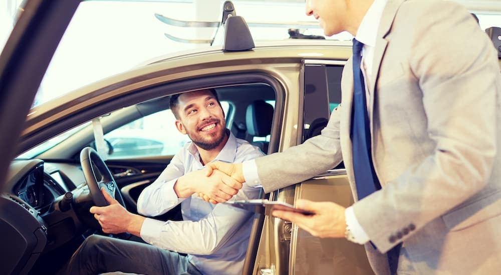 A man is sitting in a car and shaking the hand of a salesman for getting him a bad credit car loan in Ohio.