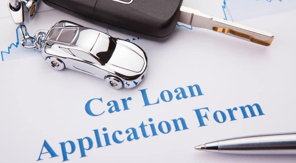 A car loan application with keys on it is shown.
