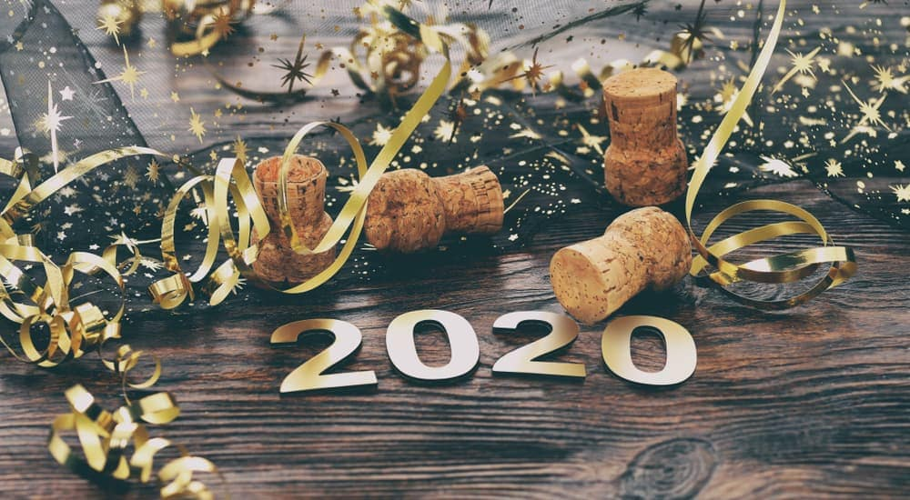 Ribbons and wine corks are behind '2020' for New Year's Eve.
