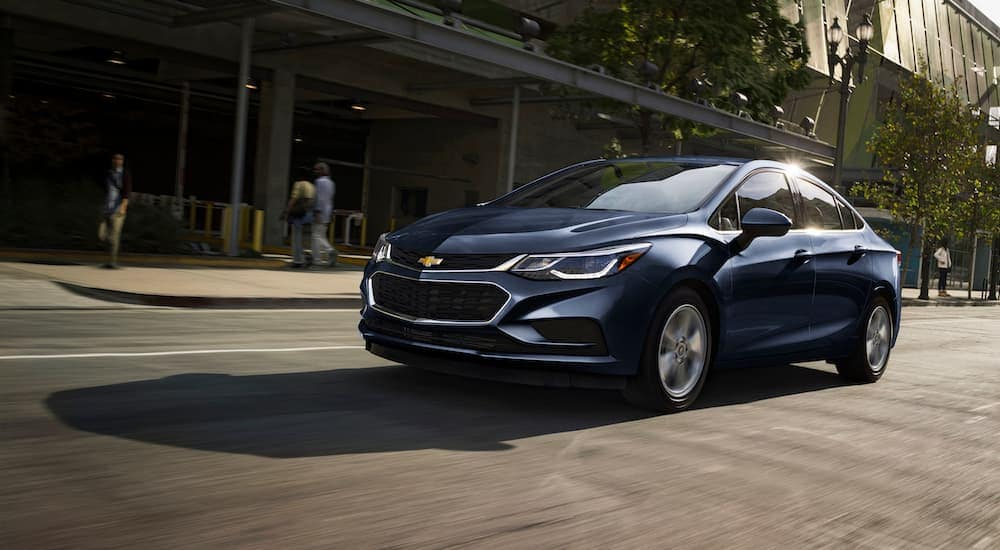 A black 2017 Chevy Cruze is driving on a busy Cincinnati, OH street.