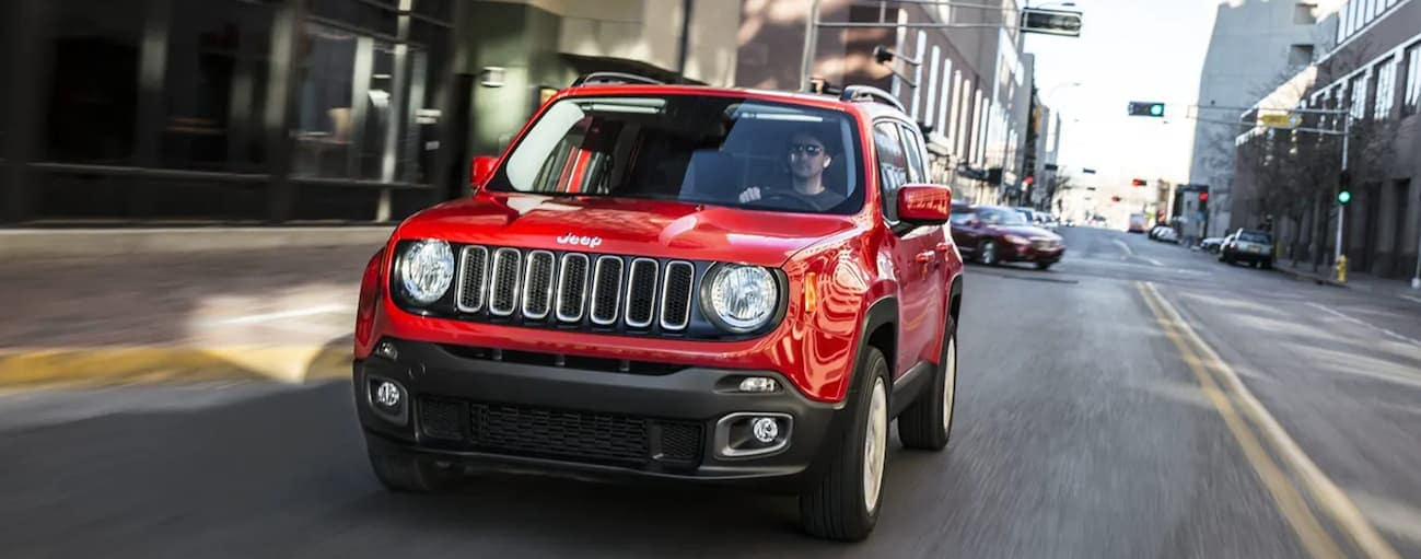 A red 2018 Jeep Renegade is driving on a busy city street near Cincinnati, OH.