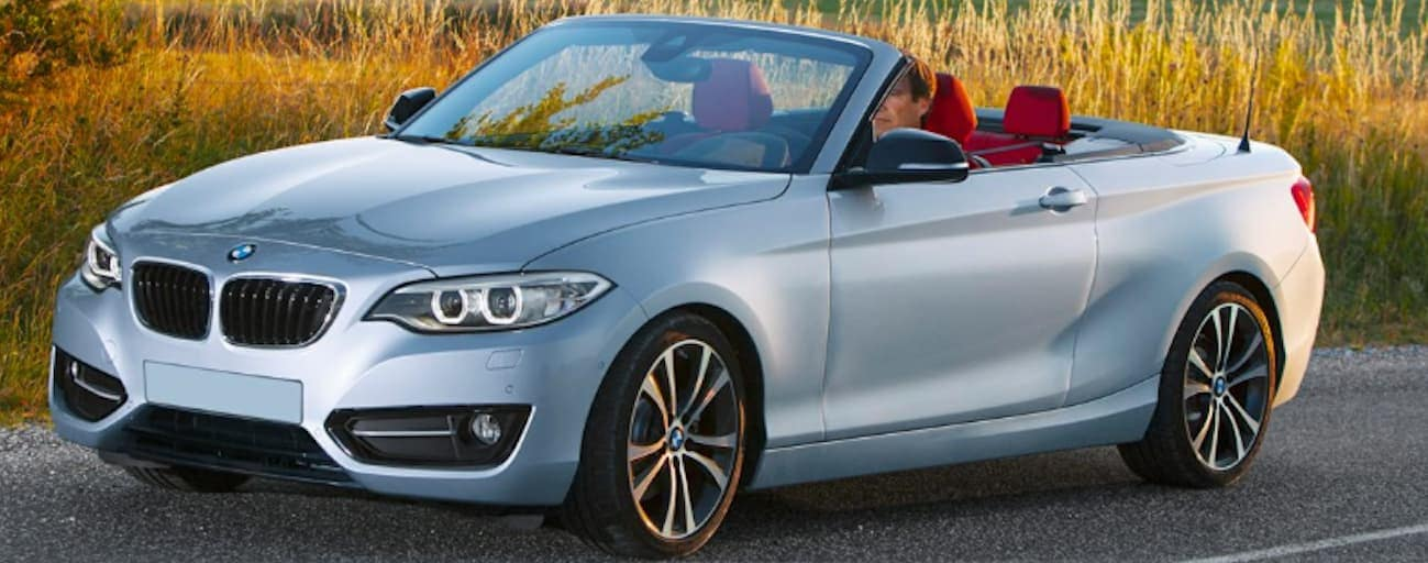 A silver topless 2015 BMW 2 Series is driving past a hay field outside of Cincinnati, OH