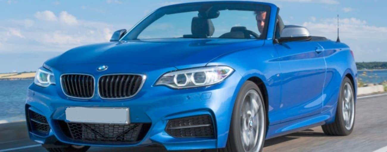 A blue 2016 BMW 2 Series is driving past a body of water on a sunny day.