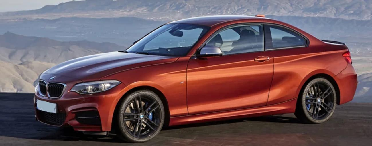 An orange 2017 BMW 2 Series is parked on a hill that is looking over mountains.