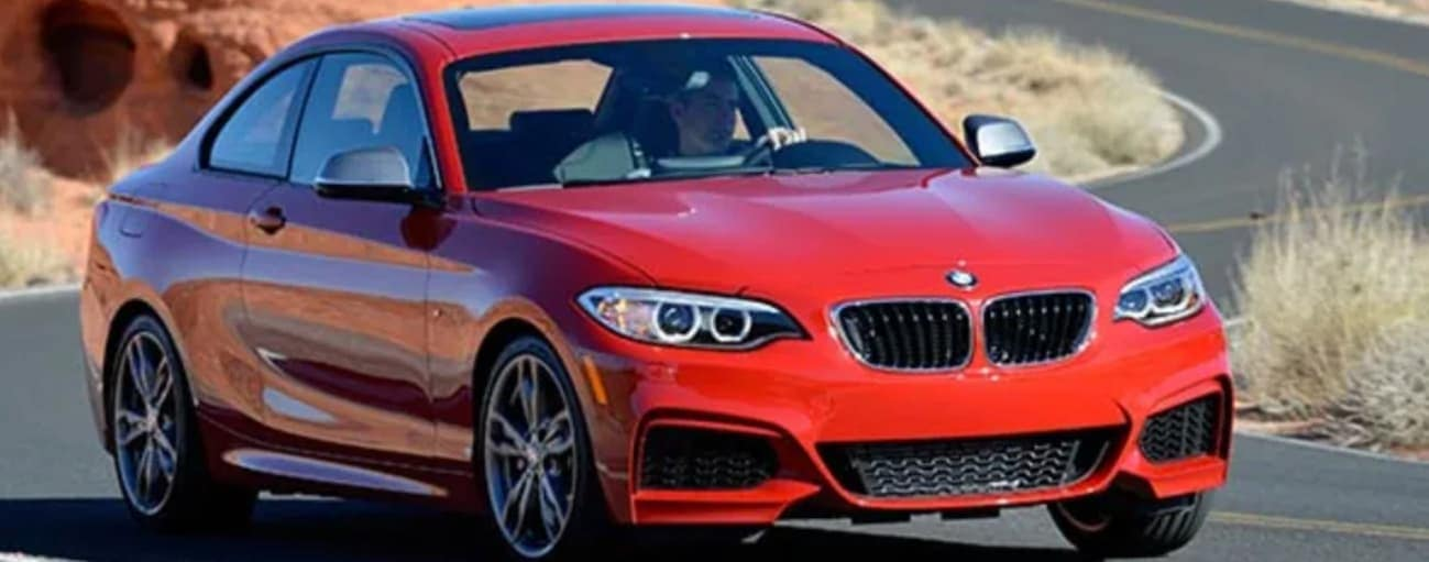 A red 2014 used BMW 2 Series is driving on a curving road.