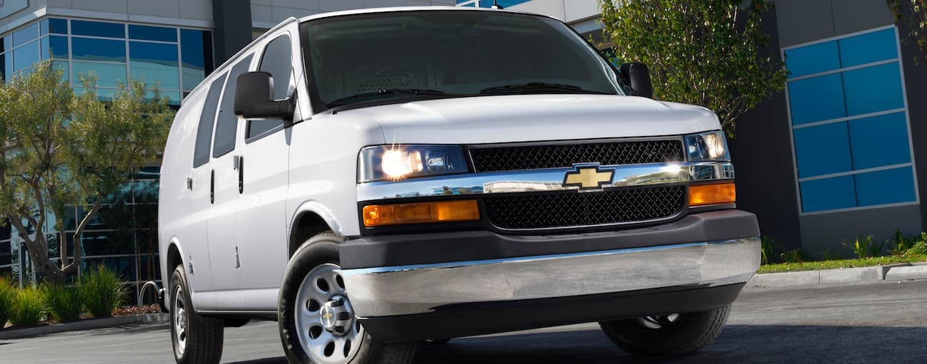 A white 2014 used Chevy Express 2500 is in front of an office building.