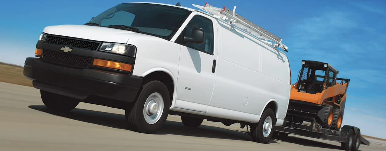 A white 2019 Chevy Express 2500 is towing heavy equipment on a highway.