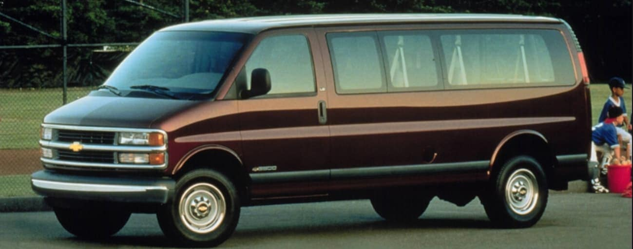 A dark red 2000 Chevy Express 2500 is parked in front of a park.