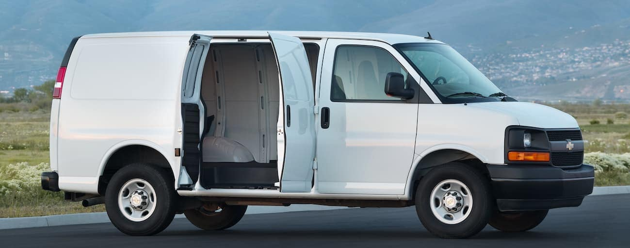 A white 2013 Express 2500 is parked with its doors open with a hilly city view.