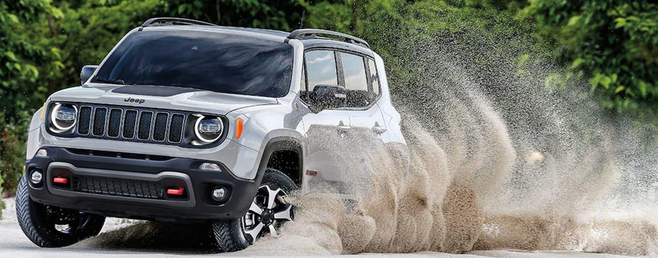 A silver 2019 Jeep Renegade is driving through sand.