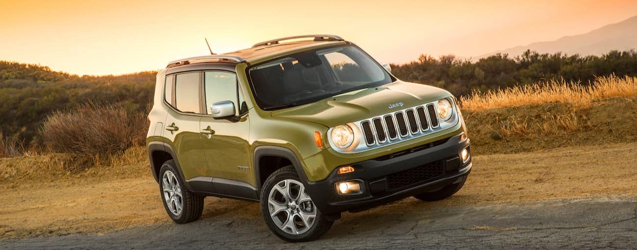 A green 2015 used Jeep Renegade is parked on the side of the road during a sunset.