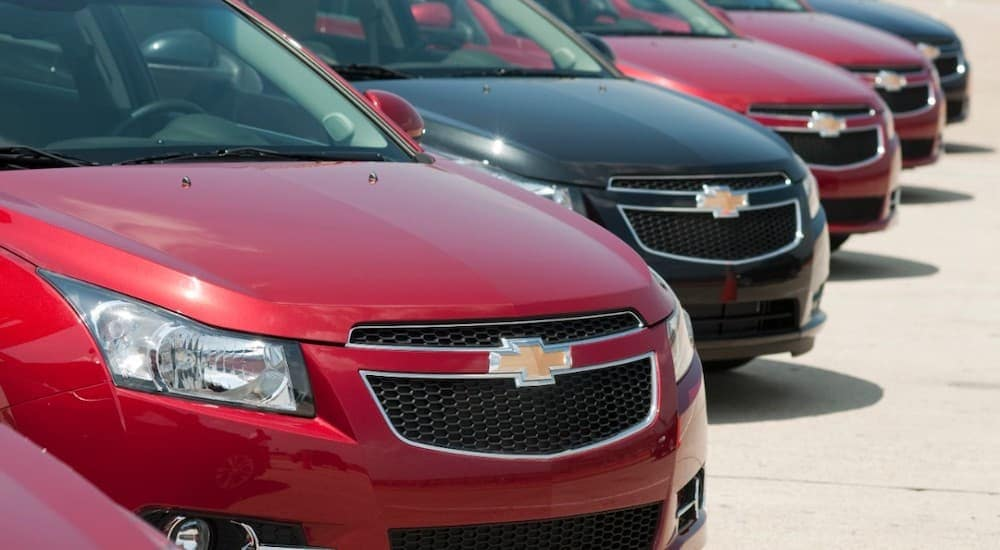 A row of black and red 2011 Chevy Cruzes are shown in a Cincinnati, OH, dealership lot.