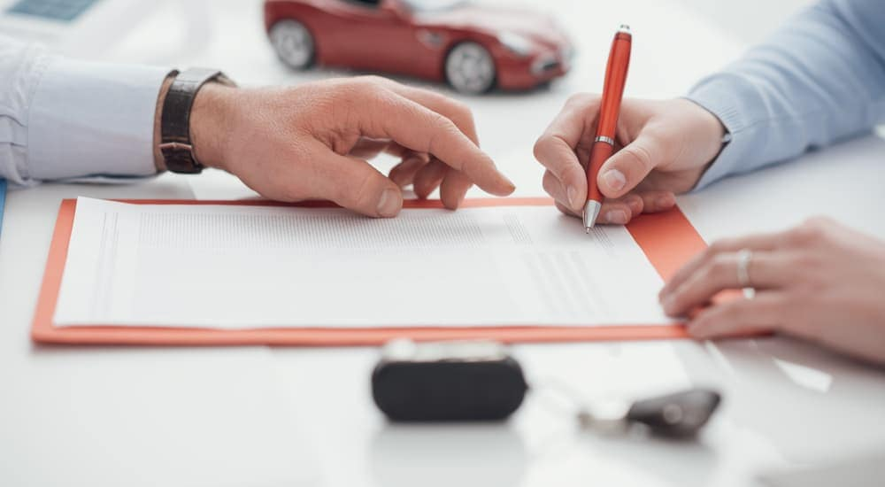 A closeup of a bad credit car loan is being signed.