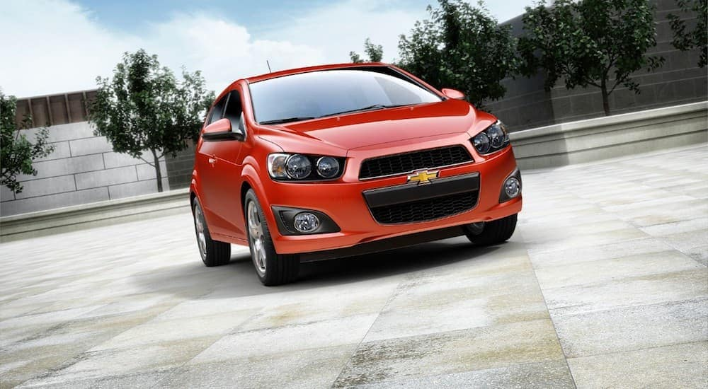 A red 2014 Chevy Sonic, a car you may find at a Buy Here Pay Here in Indianapolis, is parked in a parking lot.