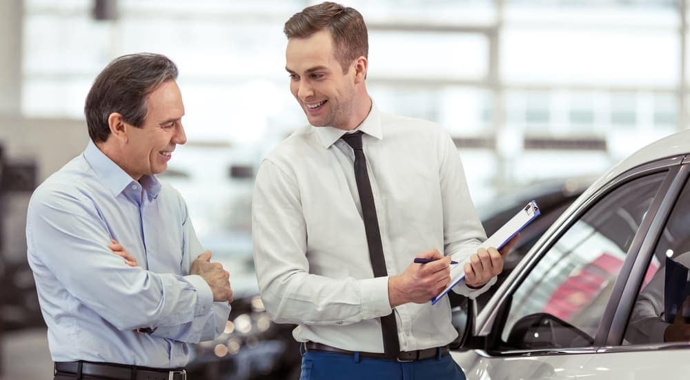 A smiling salesman is explaining paperwork to a smiling customer.