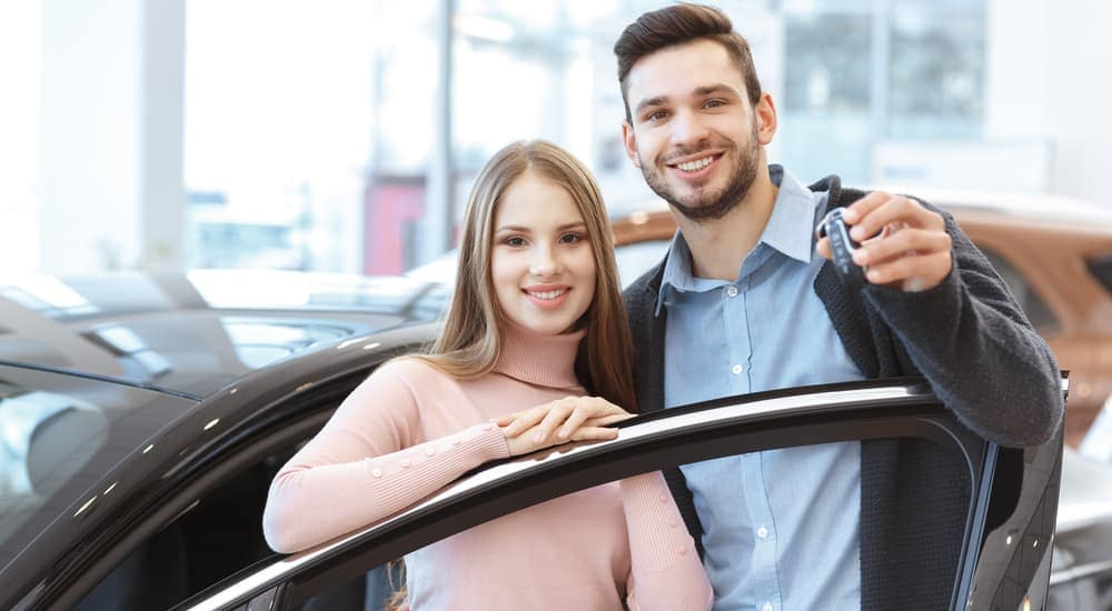 A smiling couple is holding car keys up to their new car that they bought at a Buy Here Pay Here in Indianapolis, IN.
