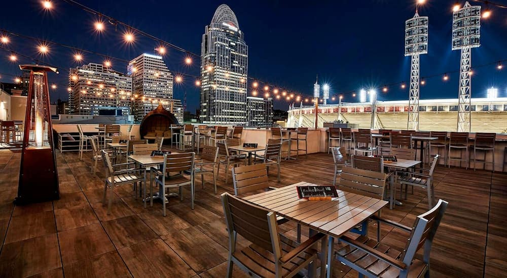 The roof deck of the AC Hotel Cincinnati at the Banks is shown at night.