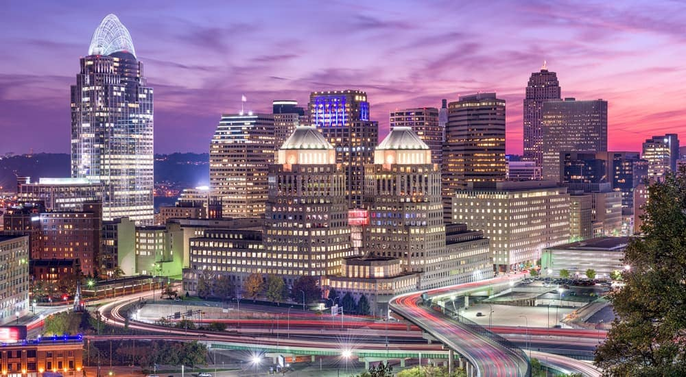 The skyline of Cincinnati, OH is lit up at sunset.
