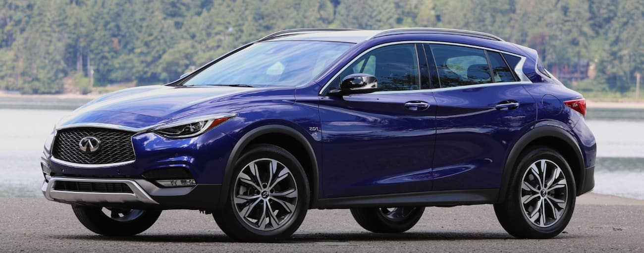A blue 2017 INFINITI QX30 is parked next a lake near Cincinnati, OH.