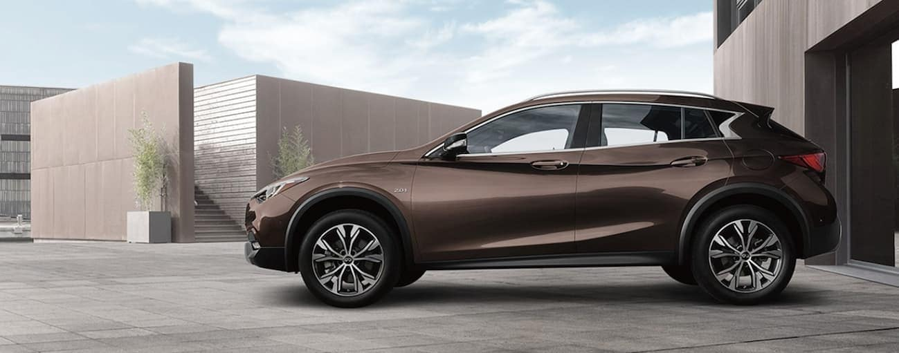 A brown 2018 INFINITI QX30, popular among used Infiniti QX30s in Cincinnati, OH, is parked in front of a building.