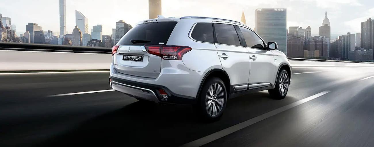 A white 2020 Mitsubishi Outlander is driving on a highway passing a city.