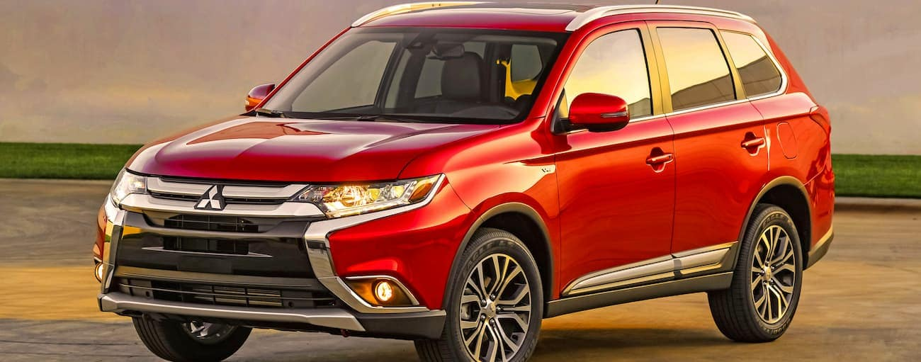 A red 2016 used Mitsubishi Outlander is parked in an open area at sunset.