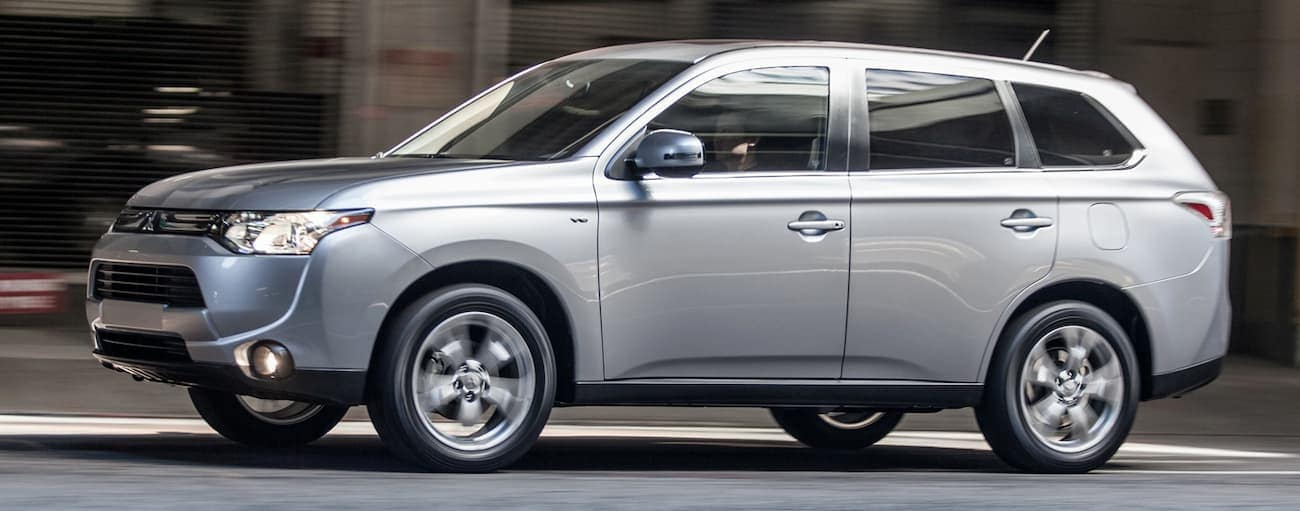 A silver 2014 used Mitsubishi Outlander is driving on a city street in Cincinnati, OH.