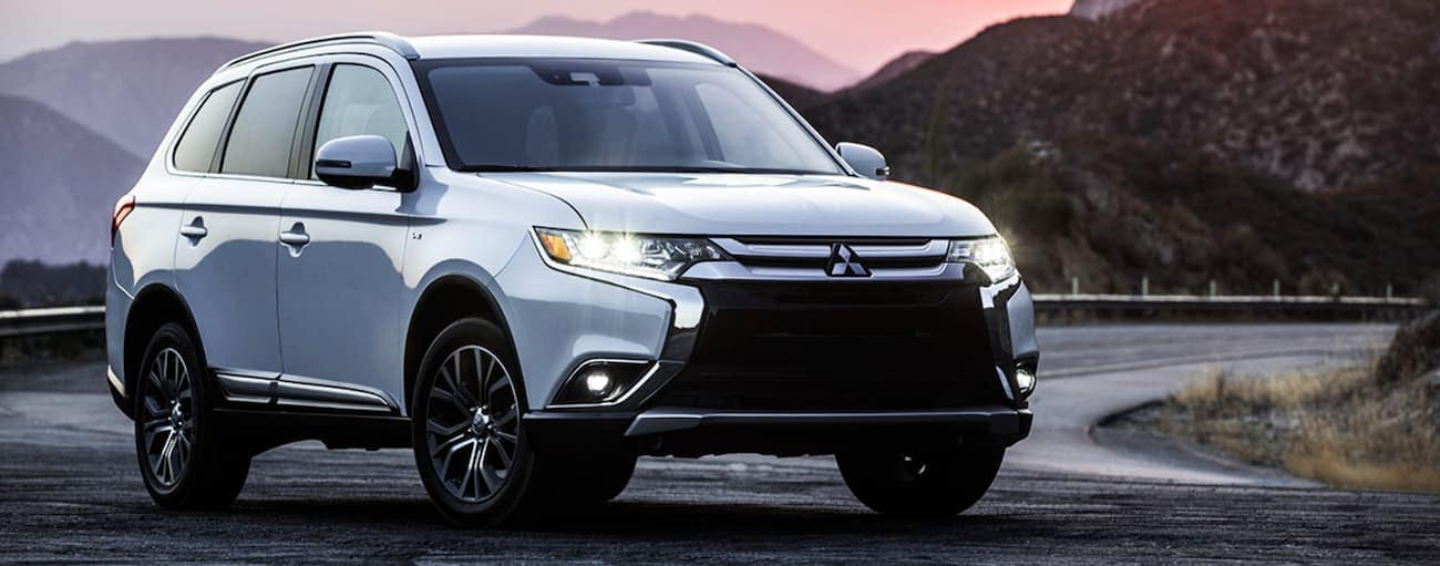 A silver 2018 used Mitsubishi Outlander is parked with mountains and a pink sky behind it.