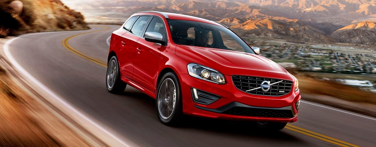 A red 2014 used Volvo XC60 is driving on a winding road with mountains in the distance.