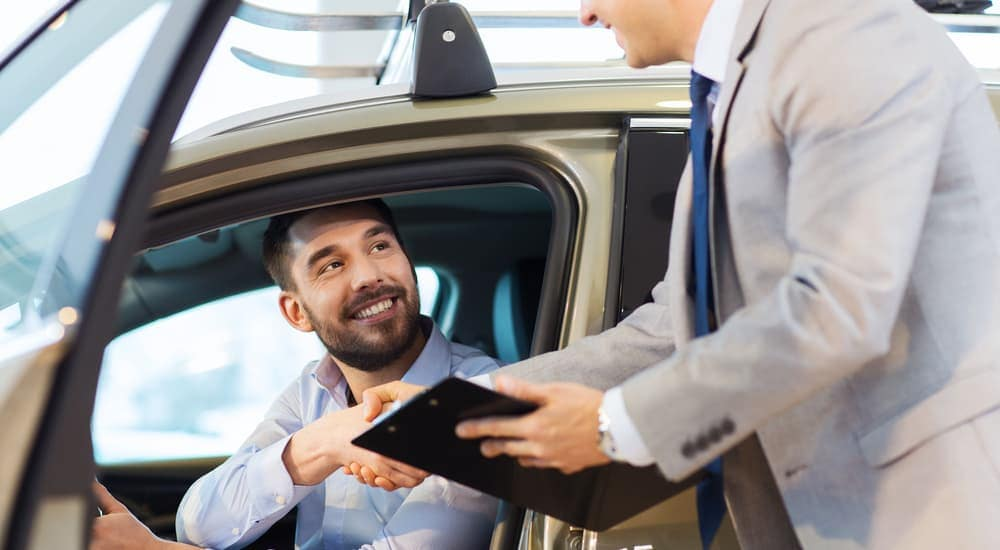 A customer who is shopping at a local buy here pay here Ohio dealership is shaking the hand of a salesman.