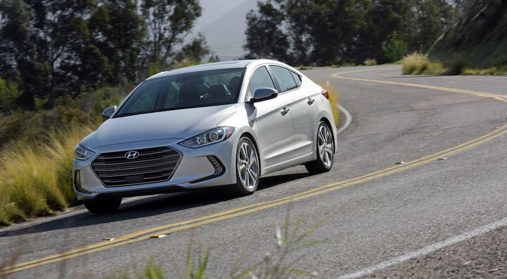 A silver 2018 Hyundai Elantra GT is driving on a tree lined road near Cincinnati, OH.