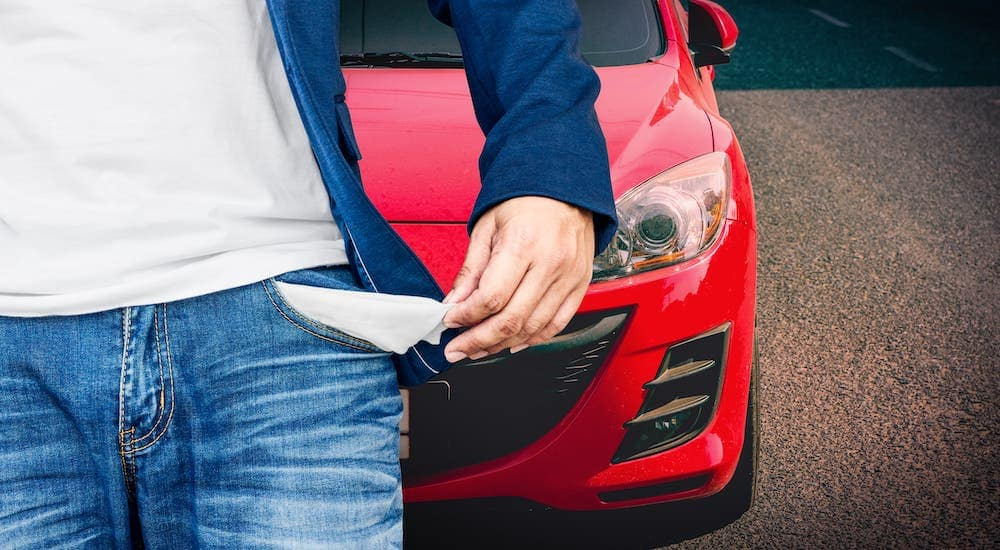 A closeup shows a turned out pocked of a man with bad credit in front of a red car.