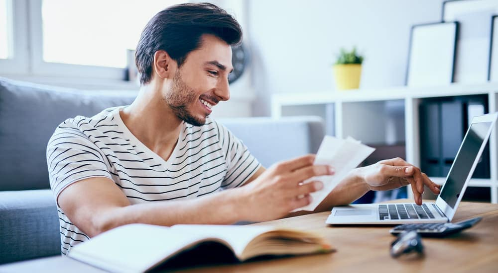 A man is smiling while he is paying off debts to fix his bad credit score.