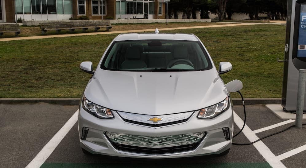 A silver 2017 Chevy Volt, which is a popular option among used cars, is parked in front of a school near Cincinnati, OH.