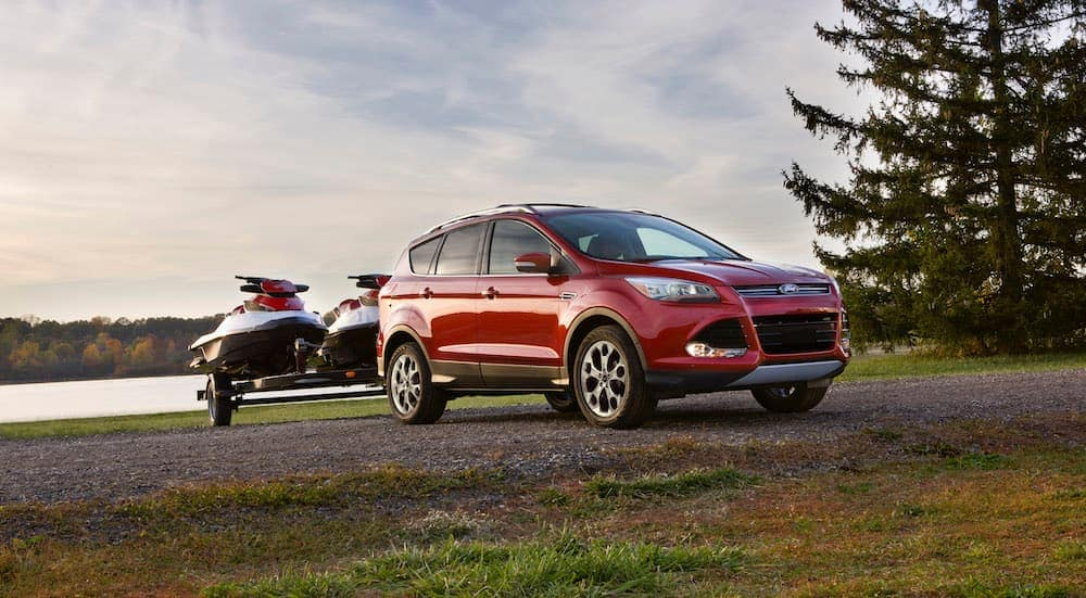 A red 2014 Ford Escape is parked in front of a lake with jetskis on a trailer.