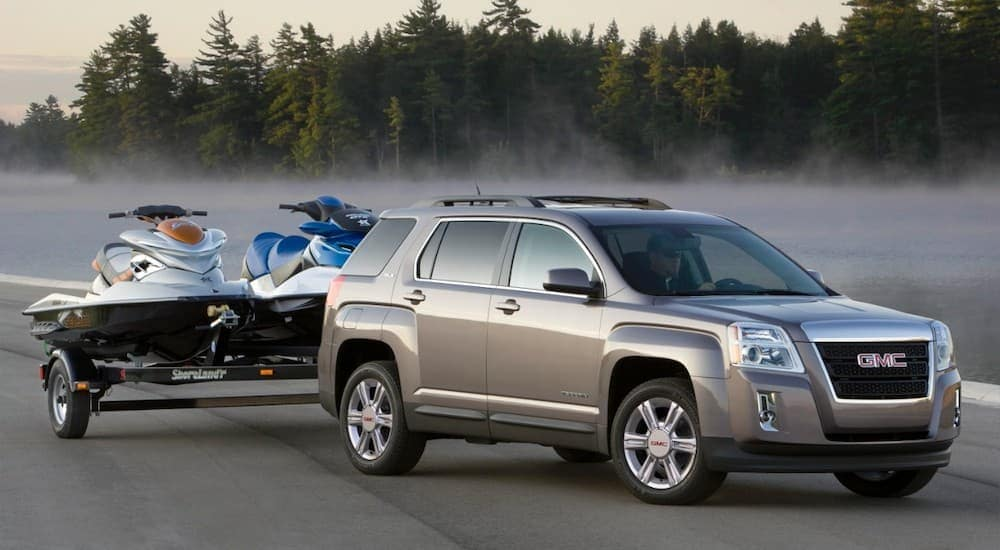 A grey 2015 GMC Terrain is parked in front of a misty pond with jetskis on a trailer.
