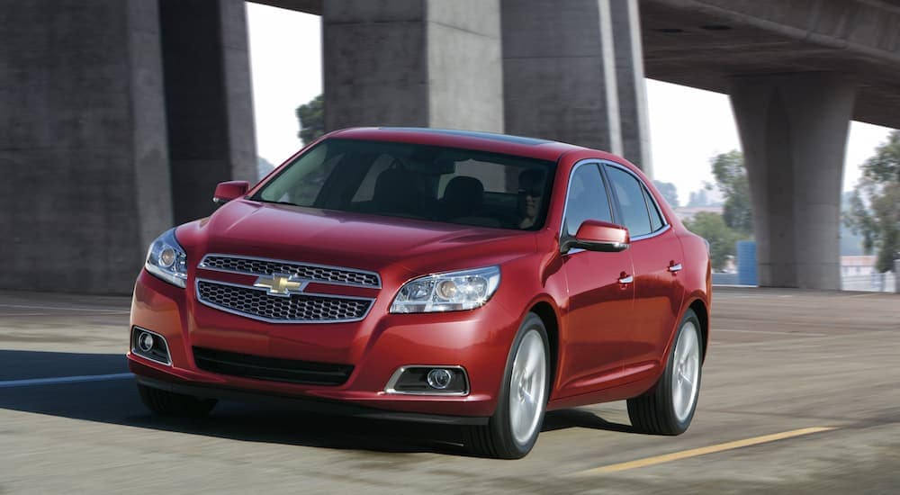 A red 2013 Chevy Malibu, which is a popular option among used cars, is driving under a Cincinnati, OH, bridge.