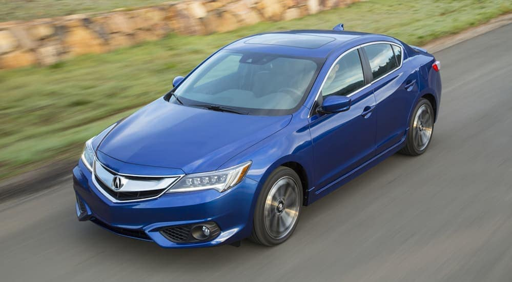 A birds eye view of a blue 2016 Acura ILX is shown driving on a grass lined road near Cincinnati, OH.