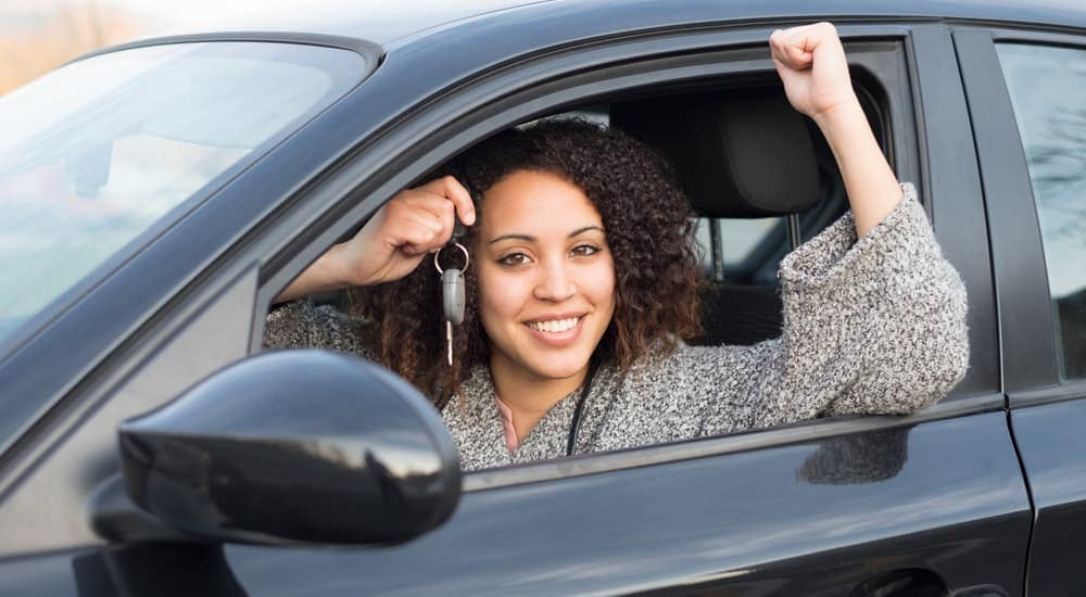 A woman is smiling as she holds up the keys to her new used car in Cincinnati, OH.