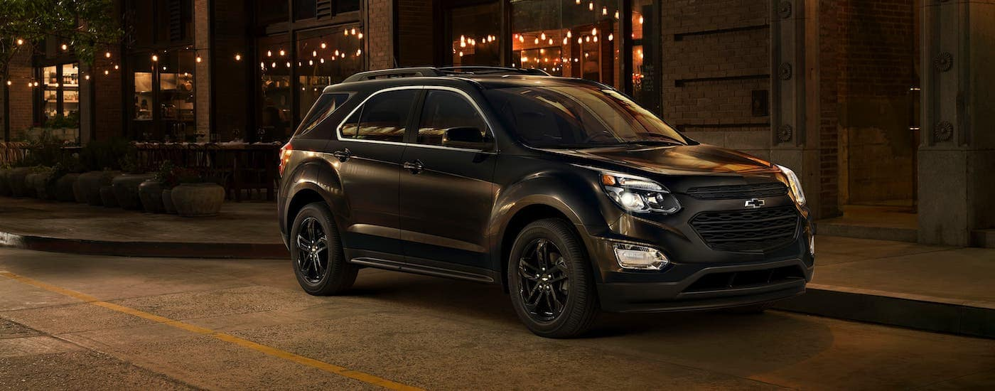 A black 2017 used Chevy Equinox Midnight Edition is parked on a Cincinnati street at night.