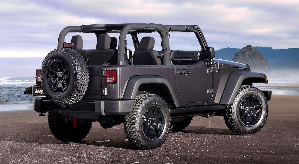 A gray 2014 used Jeep Wrangler Willy's with no roof is facing away at the ocean.